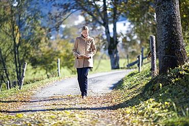 Austria, Salzburger Land, Maria Alm, Mature woman walking on autumn alley