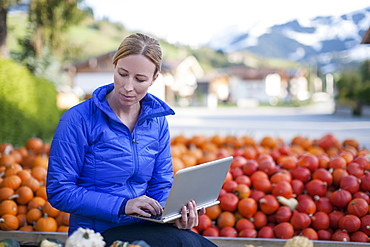 Austria, Salzburger Land, Maria Alm, Mature woman in blue jacket using laptop in market stall