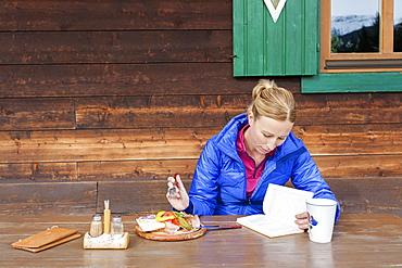 Austria, Salzburger Land, Maria Alm, Mature woman reading book during lunch