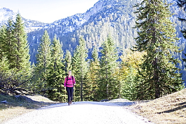 Austria, Salzburger Land, Weissbach, Mature woman hiking on sunny day in mountain landscape