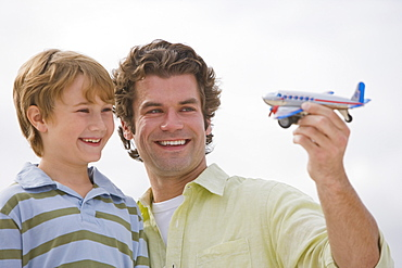 Father and son playing with toy airplane