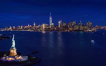 USA, New York, New York City, Manhattan, Aerial view of illuminated skyline with Statue of Liberty at night