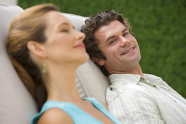 Couple laying in lounge chairs