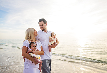Couple with twins (2-5 months) walking along seashore