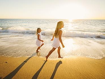 Girls (6-7, 8-9) running on beach