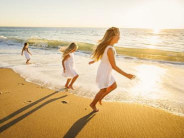 Girls (4-5, 6-7, 8-9) running on beach