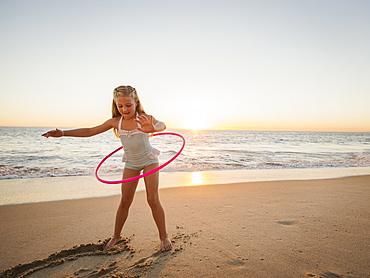Girl (8-9) spinning plastic hoop on beach