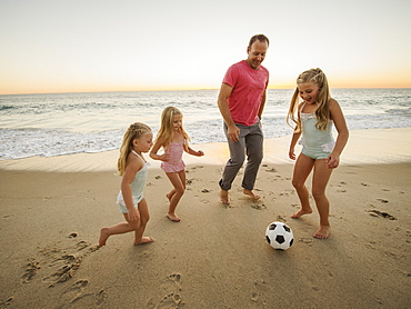 Father with children (4-5, 6-7, 8-9) playing soccer on beach