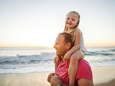 Father carrying daughter (4-5) on beach