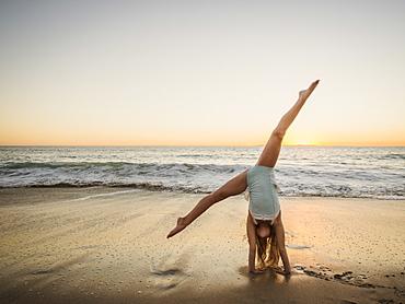 Girl (8-9) doing cartwheel on beach