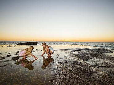 Girls (6-7,8-9) playing on beach