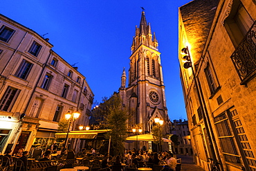 France, Occitanie, Montpellier, Sidewalk cafe and St. Anne Church at dusk