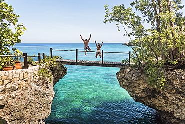 Jamaica, Negril, People jumping into ocean from footbridge