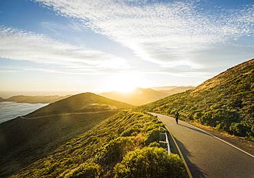 USA, California, San Francisco, California, Man walking on coastline road at sunset