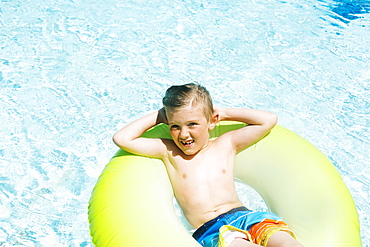 Boy (4-5) relaxing in inflatable ring