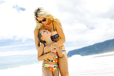 Mother and daughter (6-7) embracing on beach