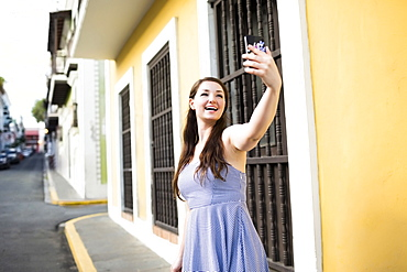 Puerto Rico, San Juan, Beautiful woman doing selfie on city street