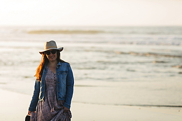 Woman in sunhat and denim jacket on beach