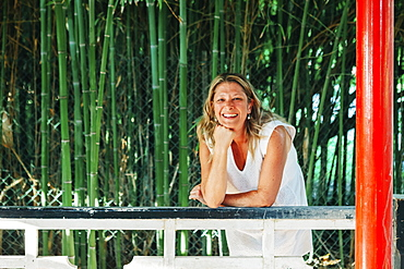 Smiling woman leaning on fence by bamboo