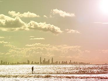 Silhouette of man paddleboarding on sea at sunset, Gold Coast, Australia