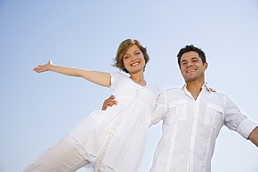 Low angle view of couple with arms outstretched
