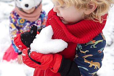 Boy holding snow heart
