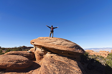 Man with arms outstretched on rock in Arches National Park, Utah, USA