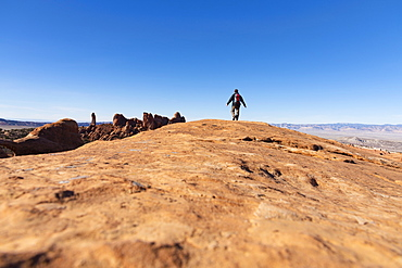 Man hiking on rock in Arches National Park, Utah, USA