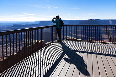 Woman taking photograph on observation point in Dead Horse Point State Park in Utah, USA