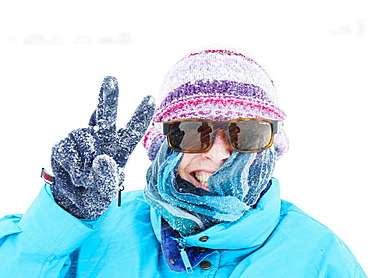 Smiling woman making peace gesture in snow