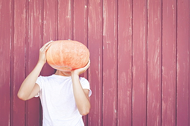 Young man holding pumpkin over his face
