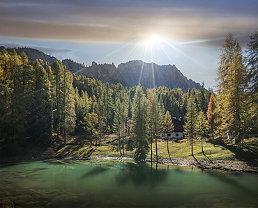 Lake and pine forest at sunrise in the Dolomites, South Tyrol, Italy