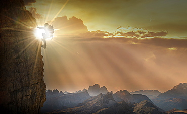 Silhouette of woman rock climbing in the Dolomites at sunrise