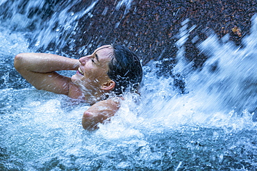 Woman with her eyes closed under waterfall in Phuket, Thailand