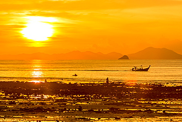 Silhouette of boat at sunset in West Railay, Thailand