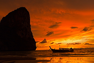 Silhouette of boat by cliff at sunset in West Railay, Thailand