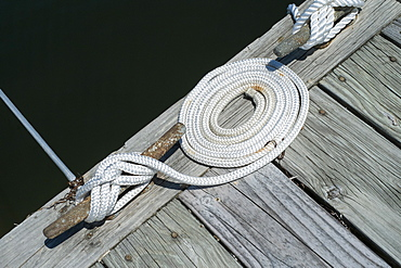 Coiled rope tied to mooring on pier