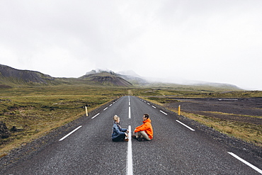Couple sitting on highway in Iceland