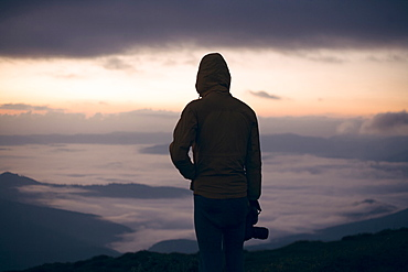 Silhouette of young man with camera at sunset in the Carpathian Mountain Range