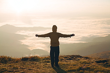 Man with arms outstretched in the Carpathian Mountain Range at sunrise