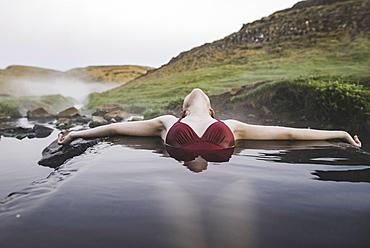 Woman bathing in hotpool in Iceland