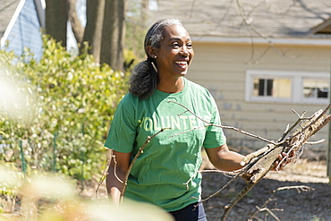 Mature woman volunteer collecting branches in garden