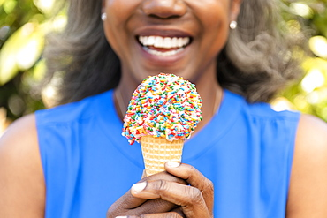 Mature woman holding ice cream cone with sprinkles