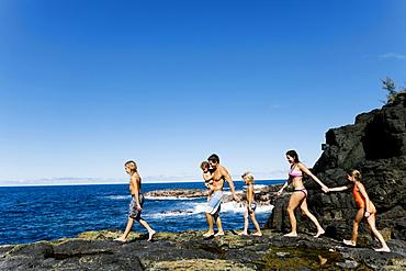Family walking on rocks by sea