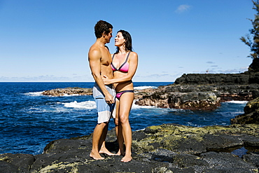 Couple embracing on rocks by sea
