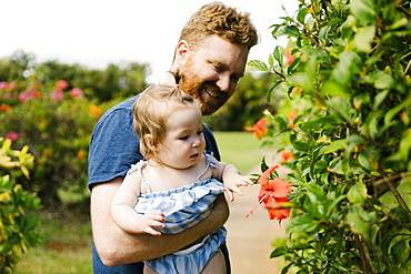 Man showing baby daughter flowers