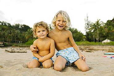 Brothers kneeling on beach