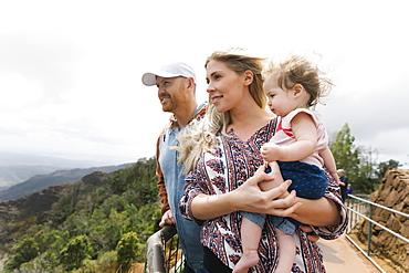 Parents with baby girl on mountain walkway