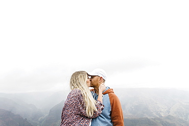 Mid adult couple kissing by mountains in mist