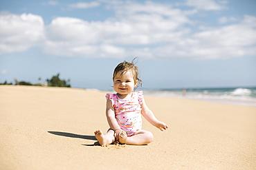 Baby girl wearing pink swimwear sitting on beach